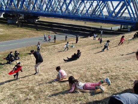 荒川で「土手滑り」イベント ござや段ボールで斜面を滑空