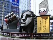渋谷・モヤイ像に巨大な「腕」出現-缶コーヒー片手に新島観光PR