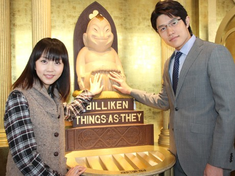 幸福の神様ビリケンさんの足の裏をなでる木南晴夏さんと鈴木亮平さん