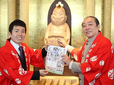 ビリケンさんの足の裏をなでる藤山扇治郎さん(左)、渋谷天外さん