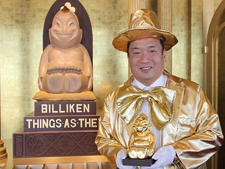 幸福の神様ビリケンさんの前でビリ金さんを持つ西上社長