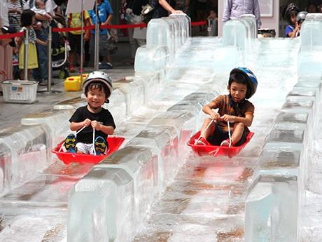 「ジャイアント氷スライダー」を滑る子供たち