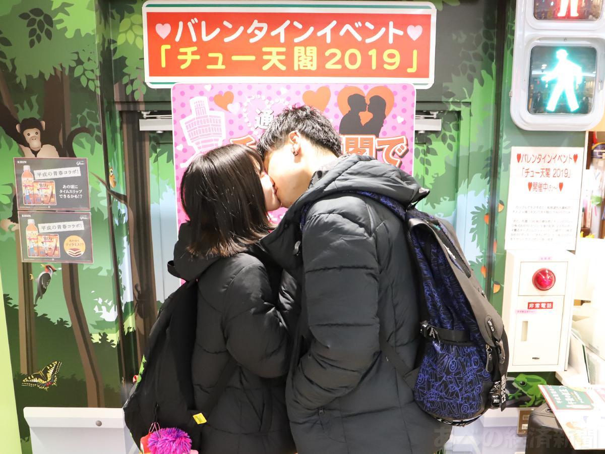 通天閣のチケットカウンター前でキスするカップル