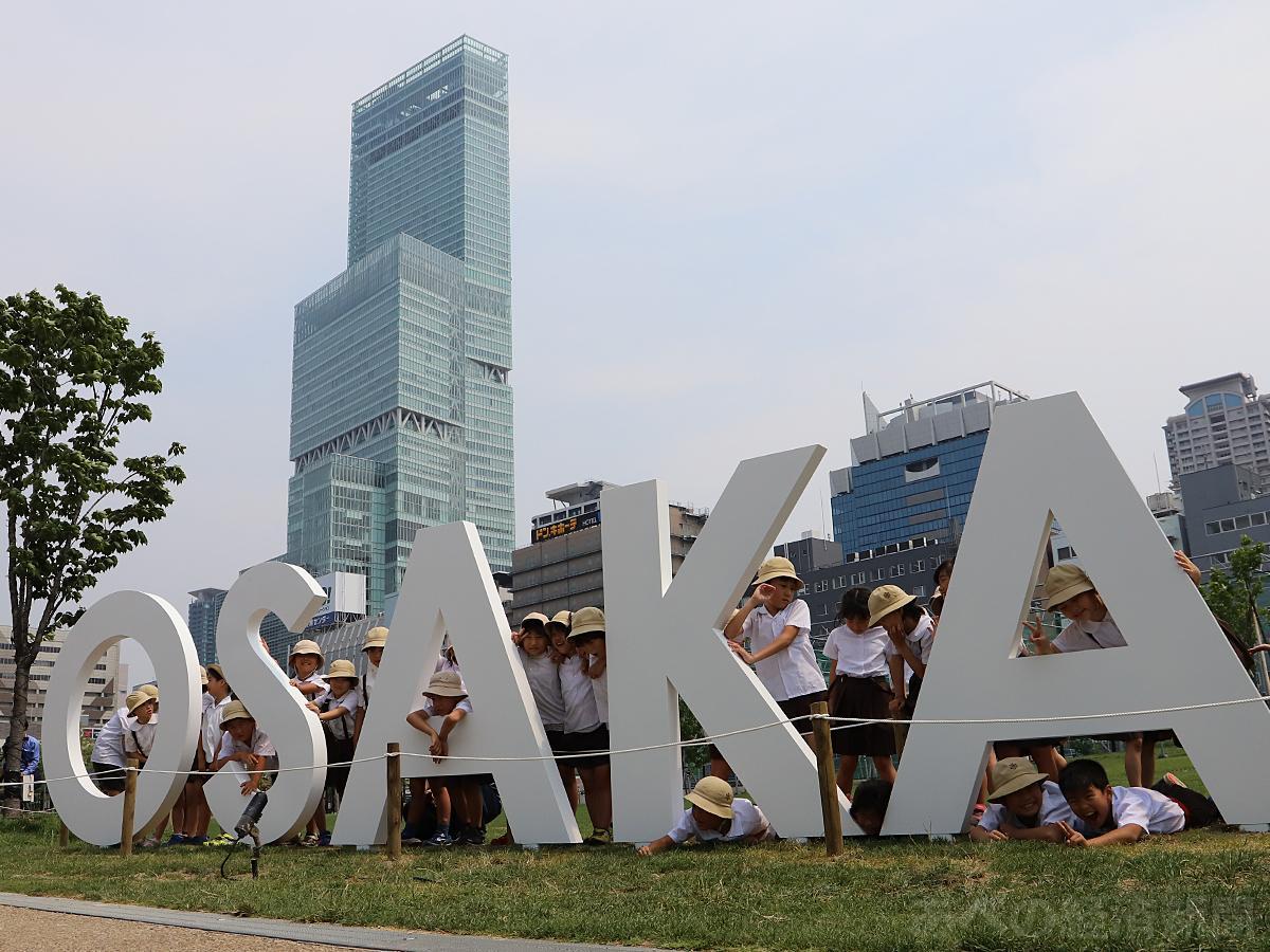 天王寺公園「てんしば」に誕生した「OSAKAモニュメント」で記念撮影する小学生たち