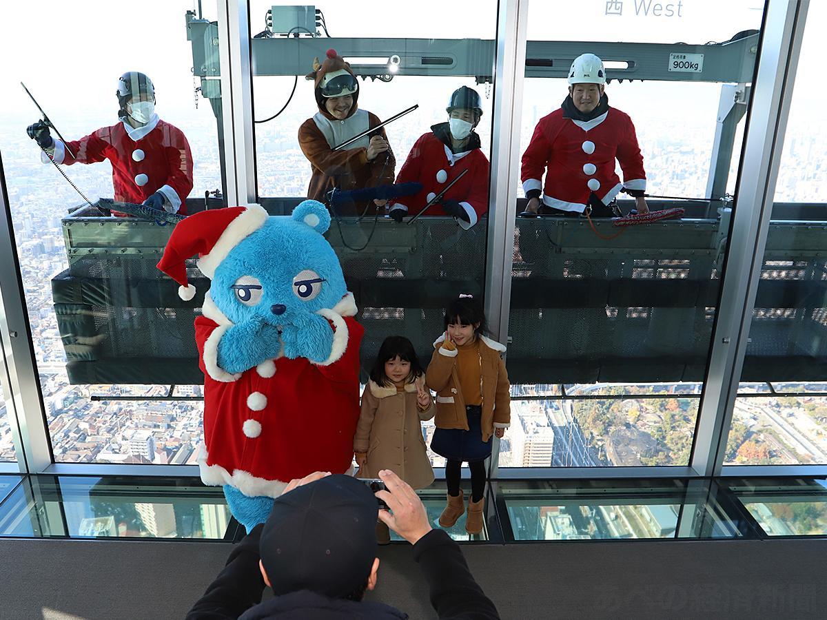 サンタクロースに扮した作業員、ハルカス300のキャラクター「あべのべあ」と来場客が記念撮影(12月9日撮影)