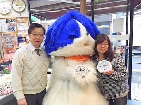 「アダチン」時計を持つアダチンとマツエ時計店の松江さん