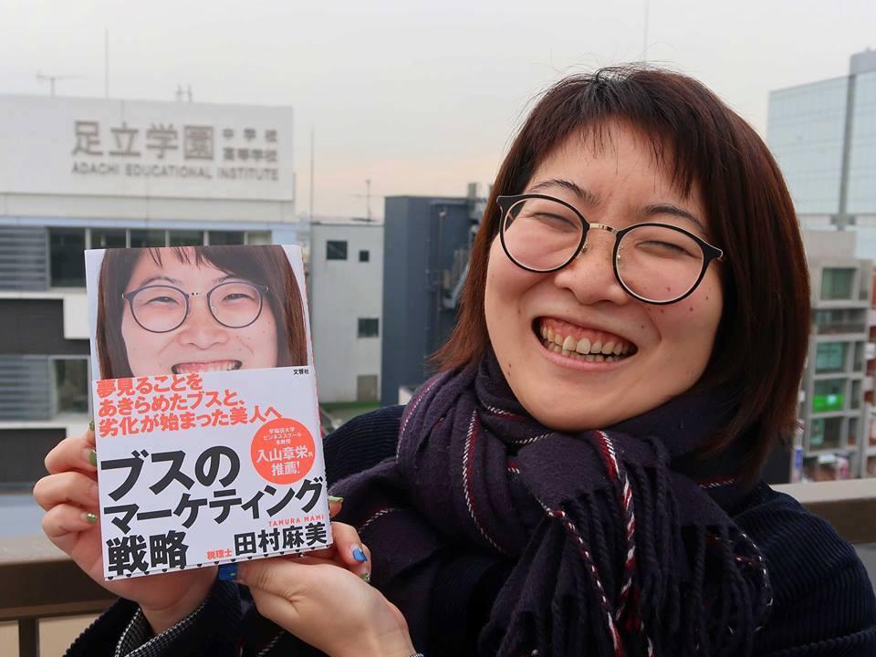 自身の本を持つ笑顔の田村さん