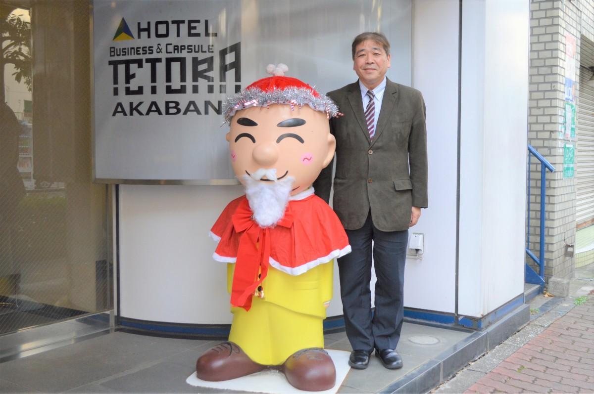 「ホテルテトラ赤羽」エントランス前の「ハゲ割人形」と根本さん