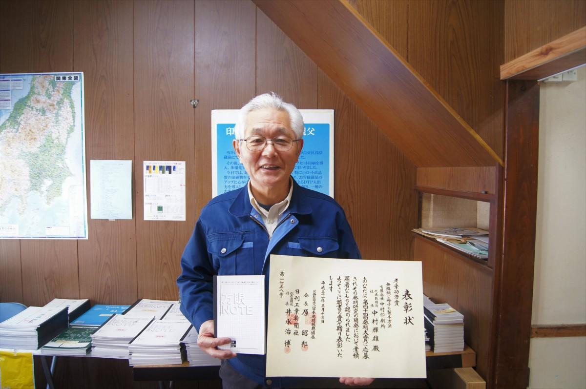 左手に発明功労賞の表彰状、右手に「おじいちゃんのノート」を持つ中村輝雄さん