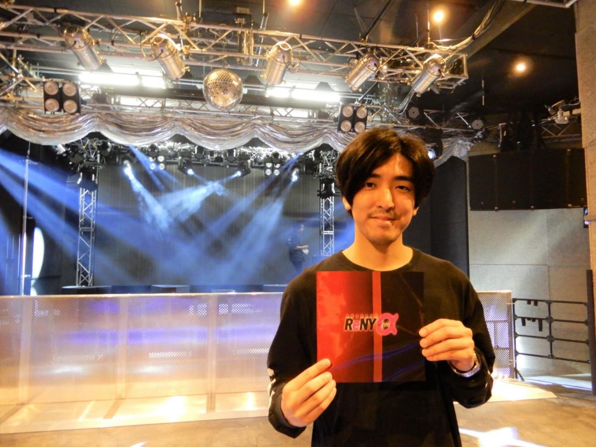 店長の岩崎さん ステージの前で