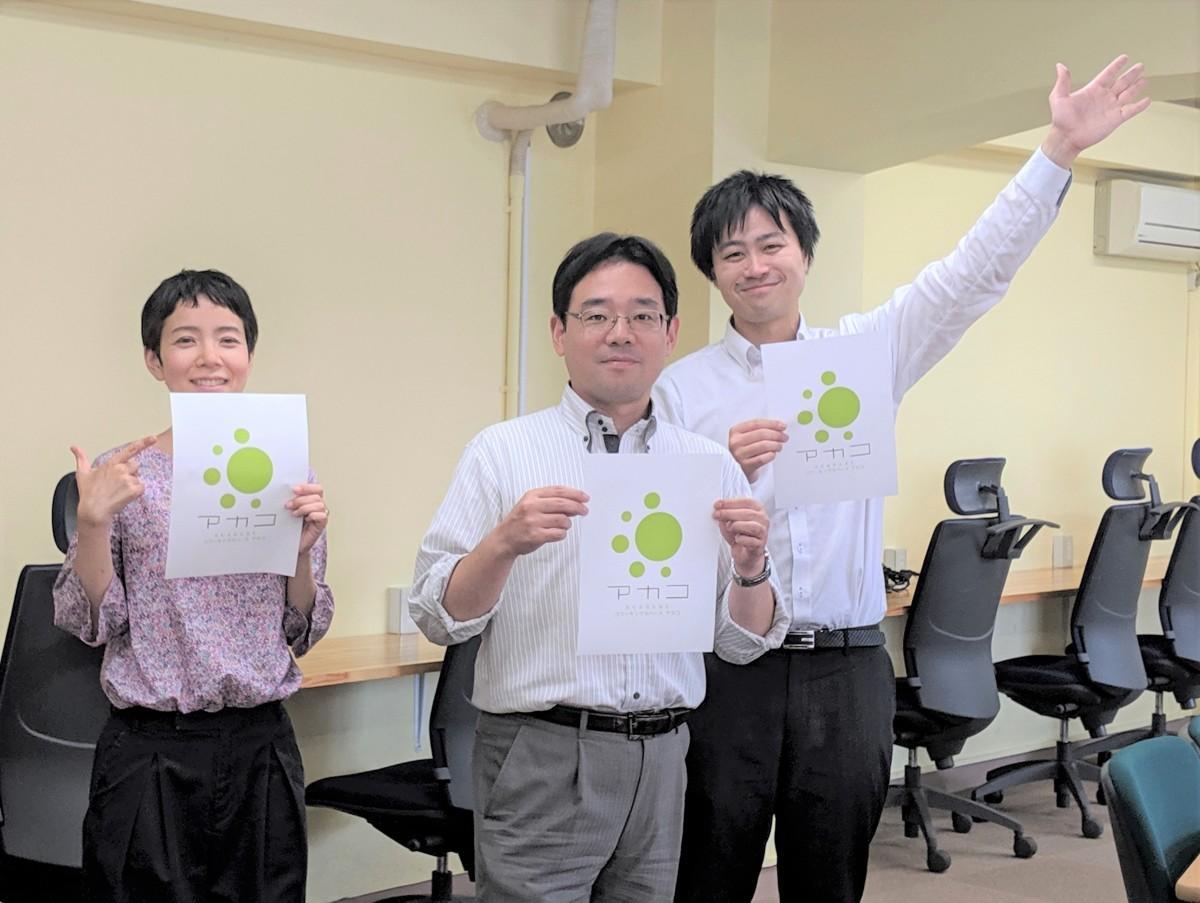 新しいロゴを持つ永沢さん(中央)とスタッフ