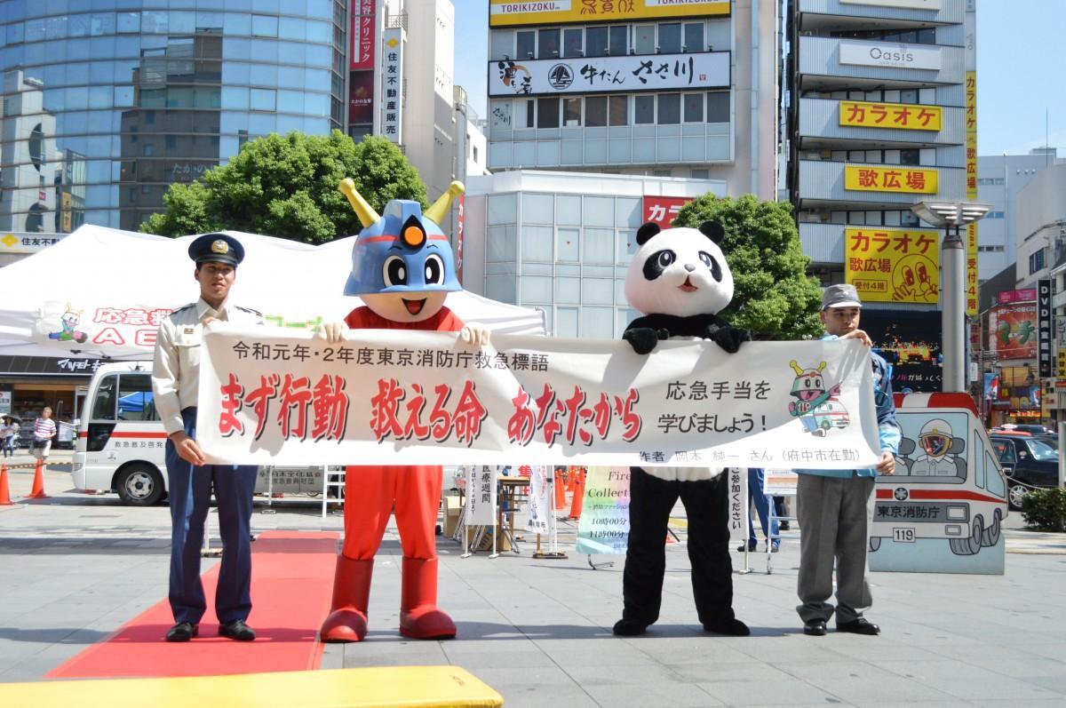 救急標語をもつキュータ(左から2番目)と消防署員