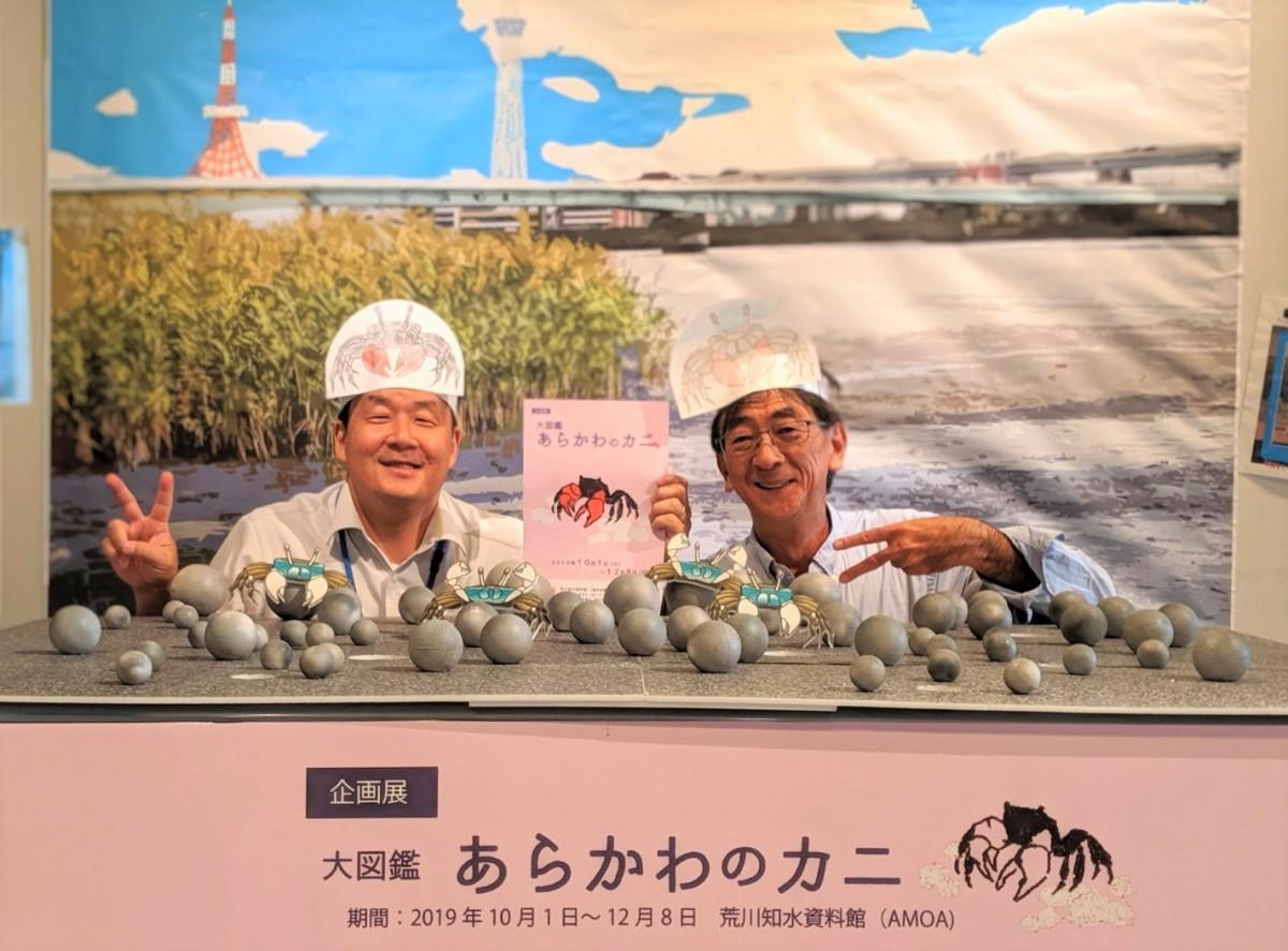 撮影スポットでカニ足のポーズで企画展をPRする藤原さん(左)と松久保さん(右)