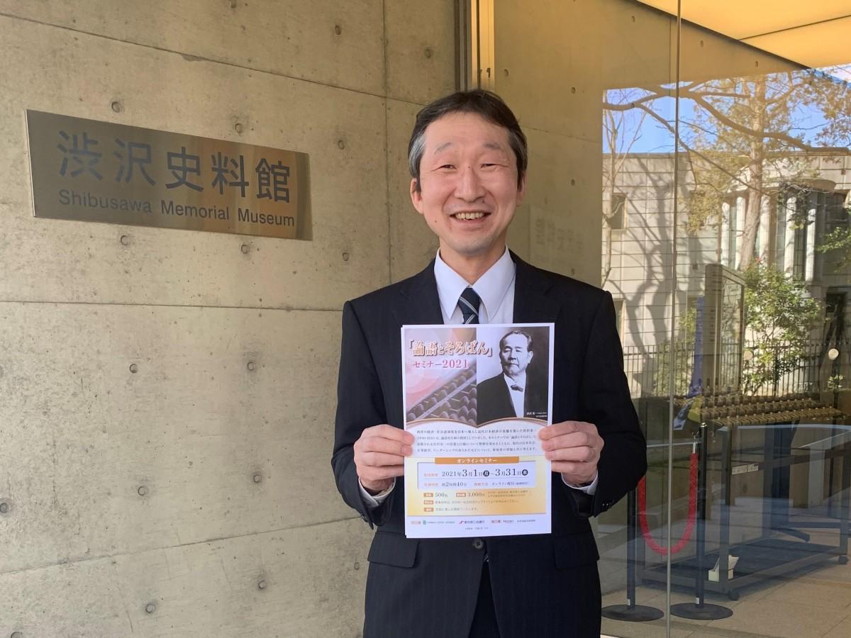 セミナーのポスターを持つ渋沢史料館副館長の桑原功一さん