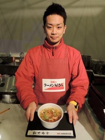 「もっちり製法」で仕上げた太麺が特徴だという「日清のラーメン屋さん 鶏炊きしょうゆ」を提供する従業員