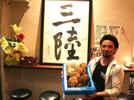 三陸から仕入れたホタテを持つ店主の吉田慶さん