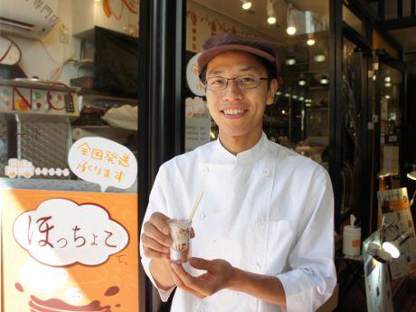ミルクを注いだショットを持つ店主の江沢孝太朗さん