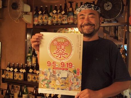 イベントのポスターを持って微笑む、参加店舗「赤坂まるしげ」店主の小久保さん