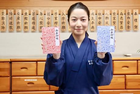 新柄「蔦」の御朱印帳を手にする販売員の女性
