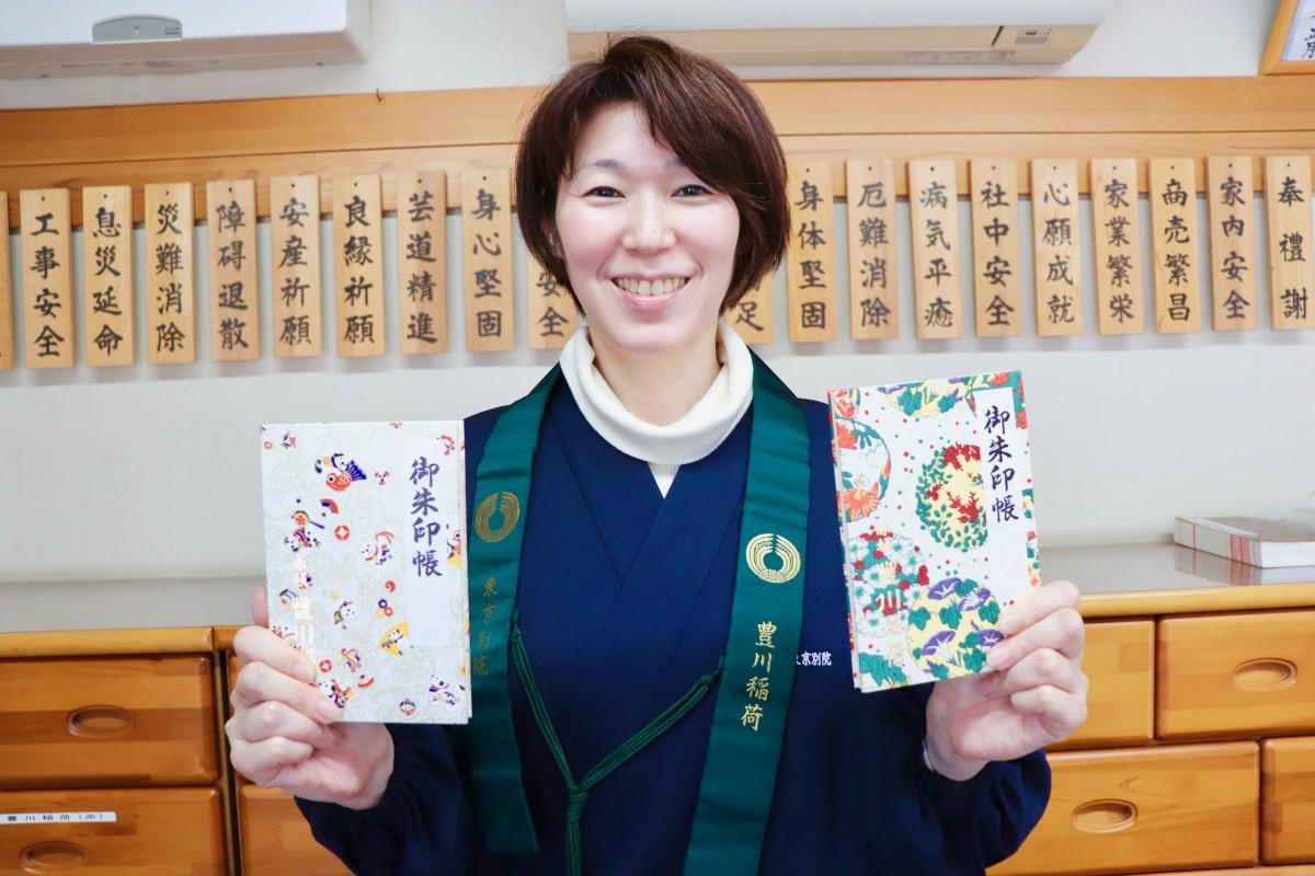 2018年元旦限定御朱印帳「戌柄」(右)、「花づくし」(左)を手にする販売員の女性