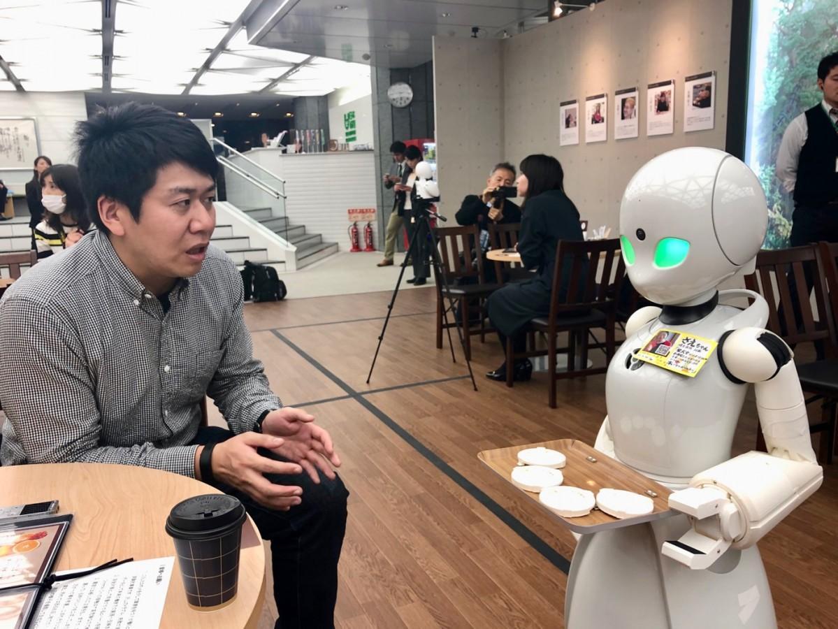 男性客に対して接客対応をするロボット「OriHime-D」
