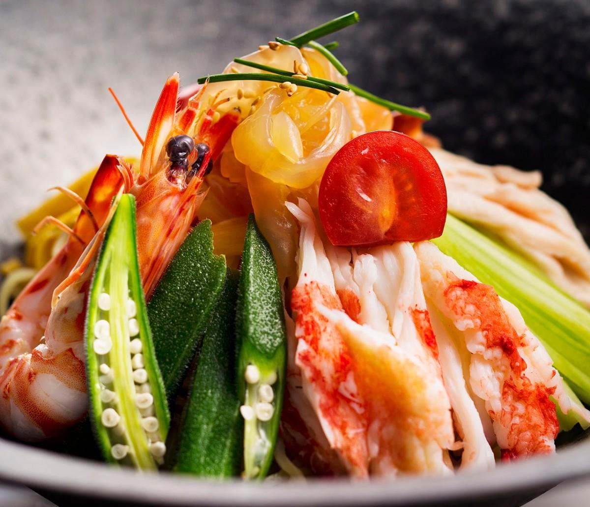 ミニトマト、オクラ、キュウリなどを添える定番の冷やしそば「花梨涼拌麺」