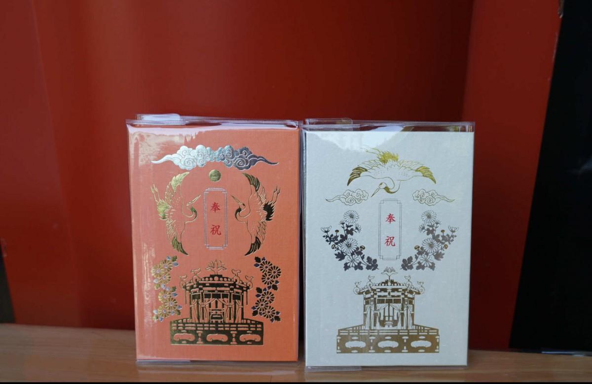 「御大礼記念御朱印帖」は白色と朱色の2種類のデザインを用意する