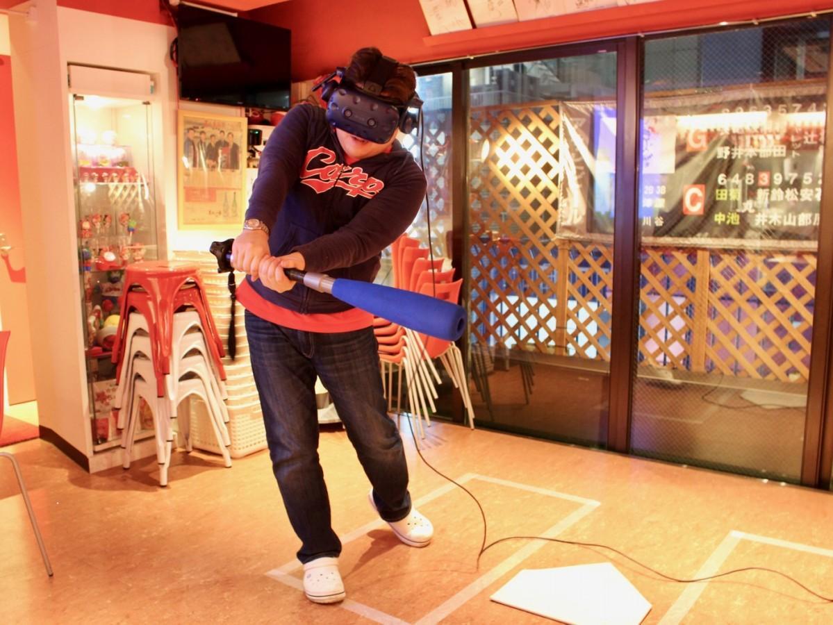 VRマシンを装着してプロの球を体験する店主の山内穂高さん