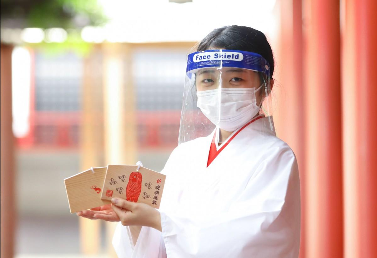 フェースシールドとマスクを付けて「日枝神社アマビエ絵馬」を紹介するみこの若森穂香さん