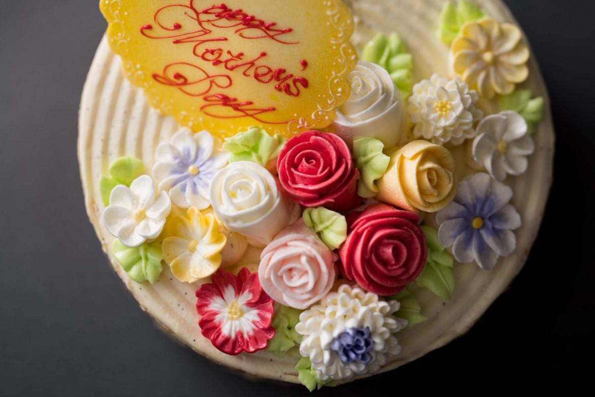 カラフルなバタークリームで花の装飾を施した「シャン ド フルール」