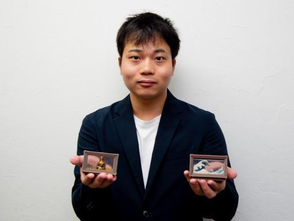 「3Dプリント名画」の「モナ・リザ」(写真左)と「神奈川沖波裏」(右)を手にするメルタ濱中拓郎社長
