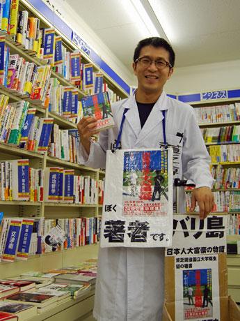 理系学生らしく白衣を身にまとって自著をPRする黒岩将さん。秋田市の加賀谷書店で