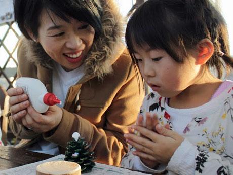 松ぼっくりを使ったクリスマスツリーづくりに挑戦する親子