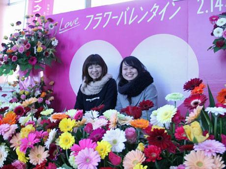 バレンタインデー向け生花のオブジェ前で記念撮影する女性