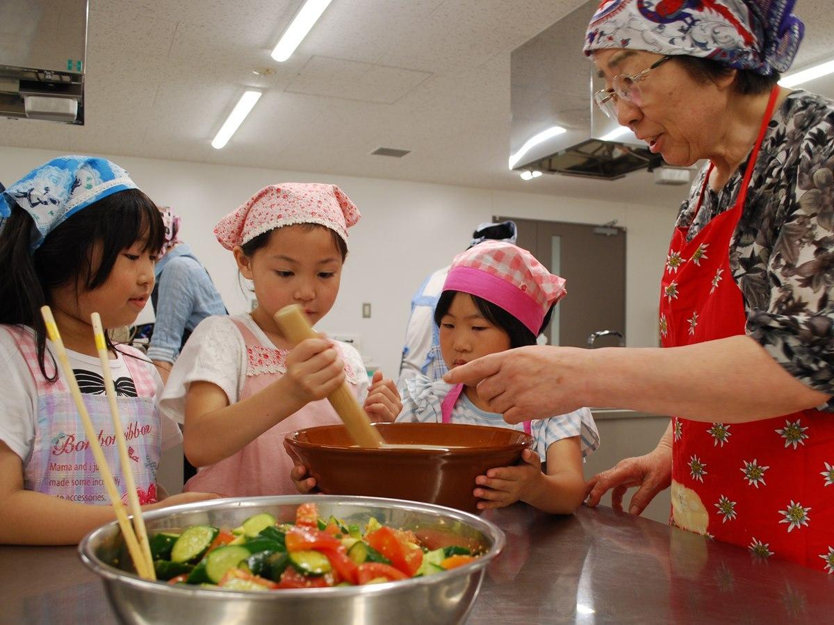 「子ども食堂」スタッフから調理を学ぶ小学生