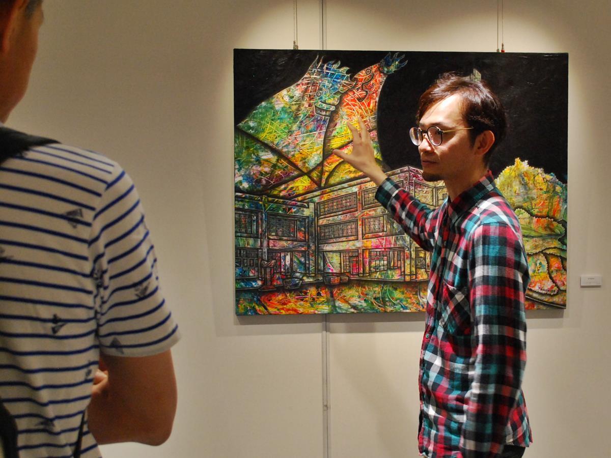 観覧者に作品を解説する秋田市出身でドイツ・ベルリン在住の画家・石塚智寿さん