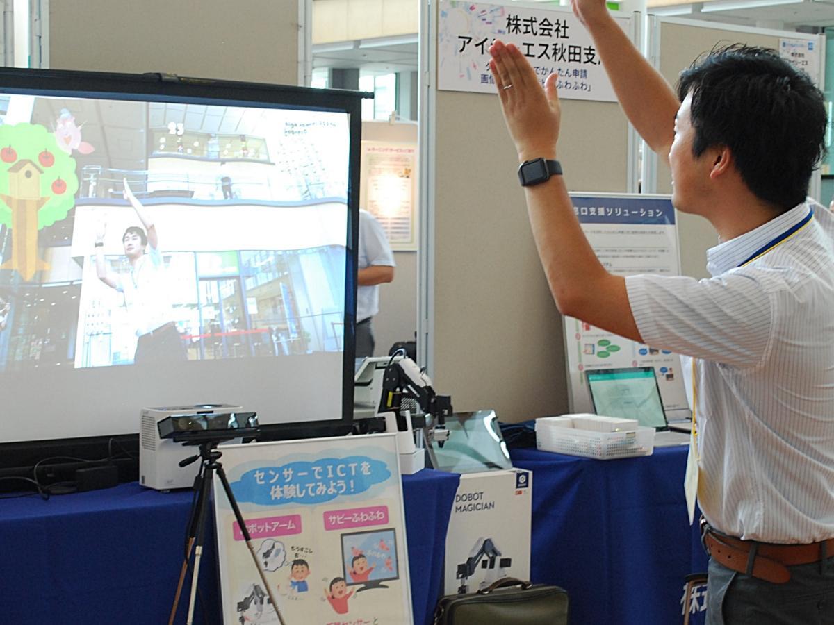 体の動きをスクリーンに取り込む技術を活用したゲームをデモンストレーションする出展社の担当者