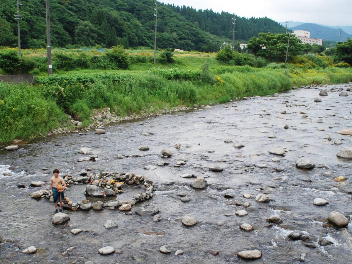 鹿角市内を流れる大湯川で「ストーンサークル」がモチーフの作品を発表するワークショップ参加者