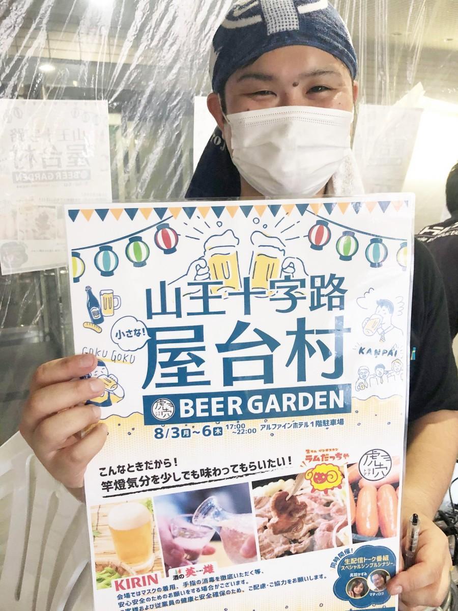 秋田市山王十字路前のビジネスホテルで開催中の「山王十字路屋台村」をPRする運営スタッフ