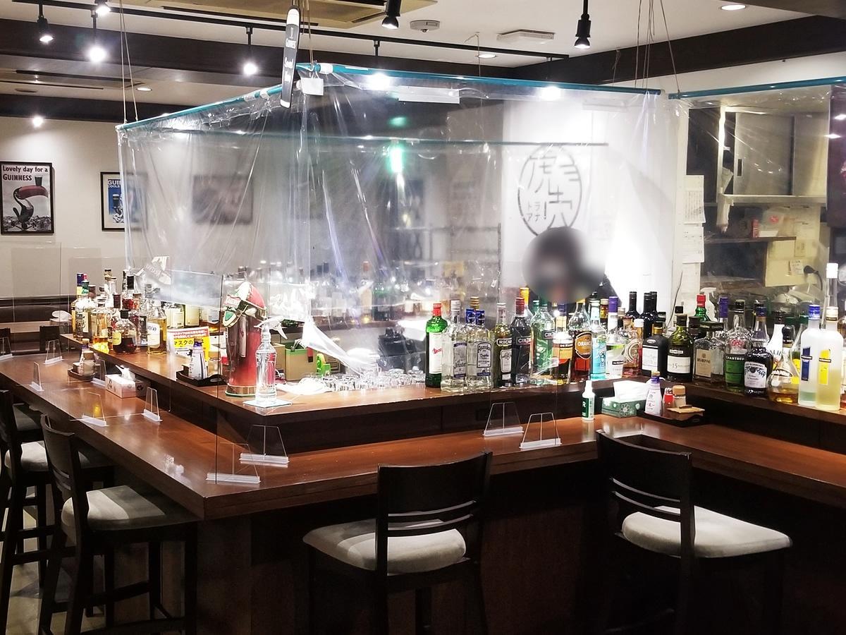 カウンターに洋酒ボトルが並ぶ居酒屋「虎穴~featuring TIGER MORE」店内