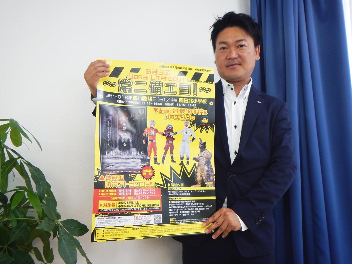 ポスターを掲げる岡本さん