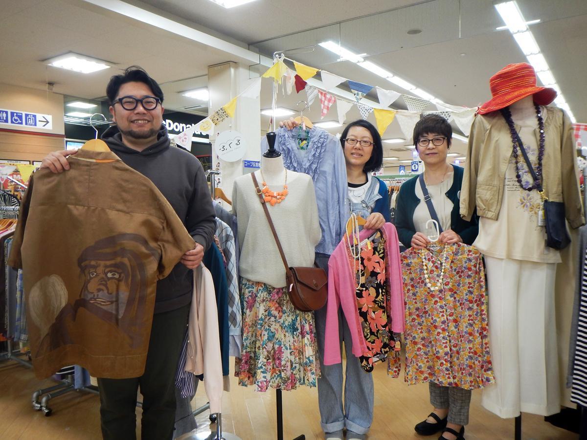 「ずっと気になっている」というダルマのシャツを手にする清田さんとスタッフの皆さん