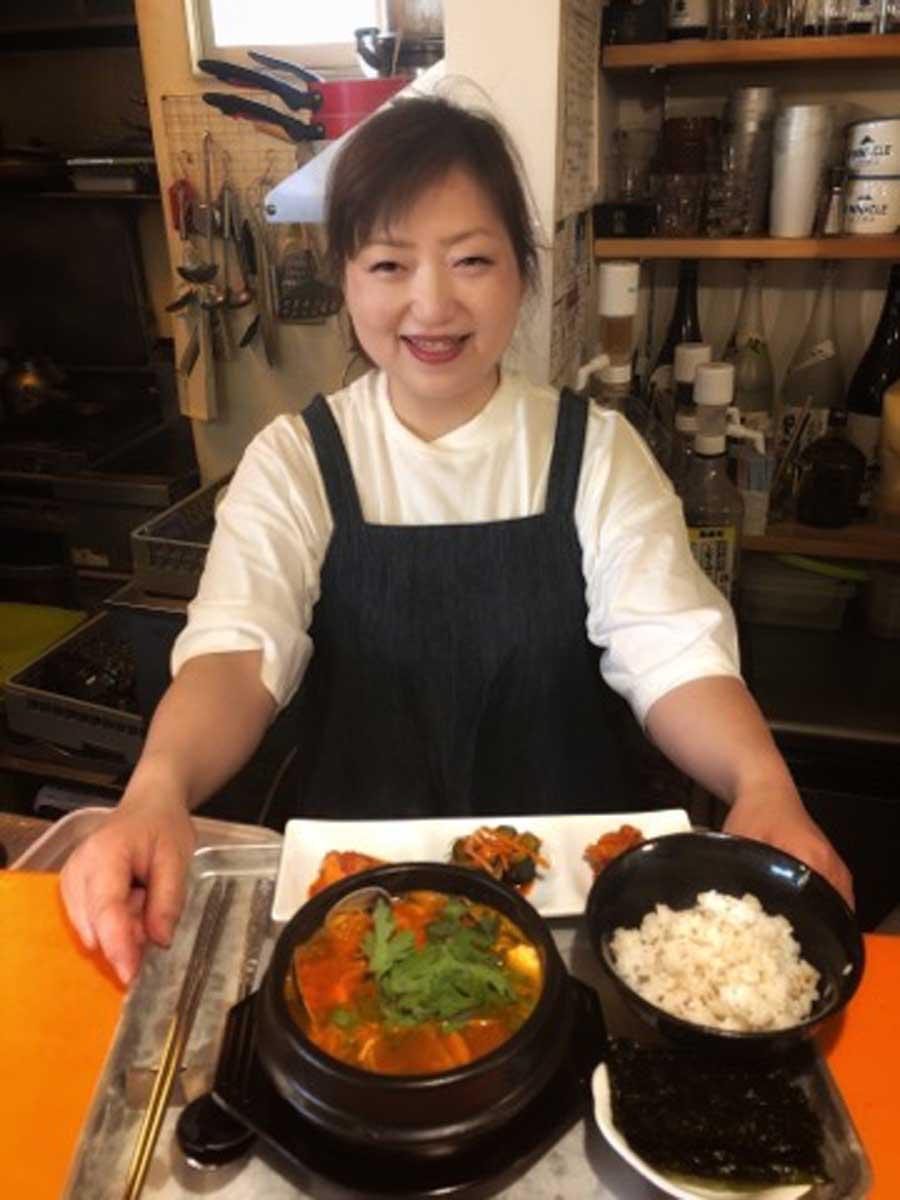 「スンドゥブ定食」を手に笑顔の安東貞恵さん