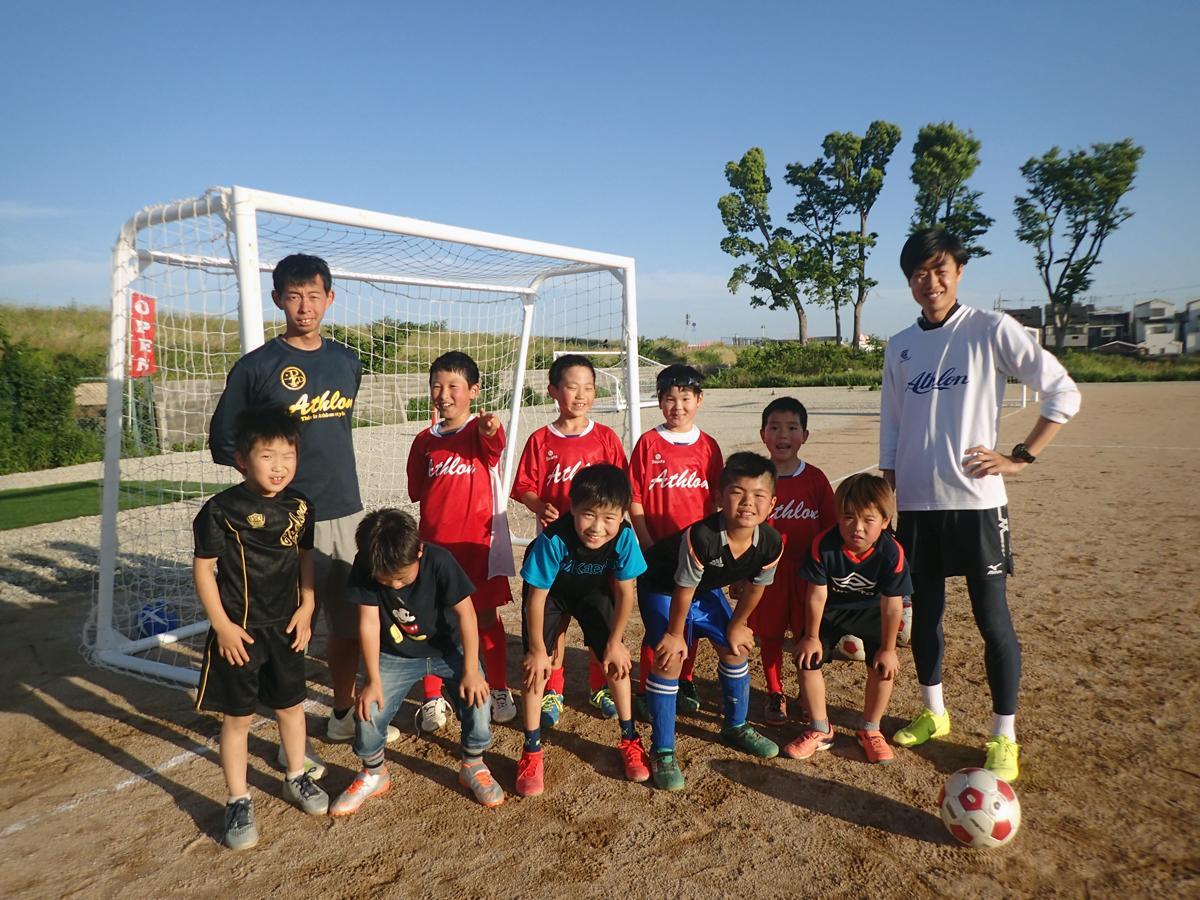 コーチの佐々木亨さん(左)と関駿文さん、小学生サッカークラスのメンバーら