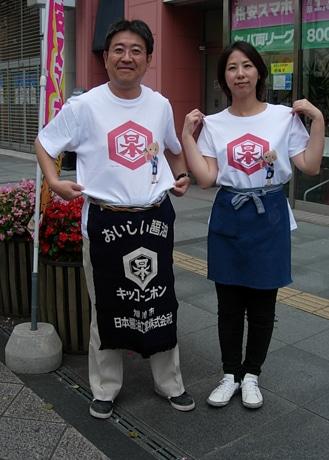 限定オリジナルTシャツを着て来場を呼び掛ける鈴木さん(左)と店長の髙垣さん(右)