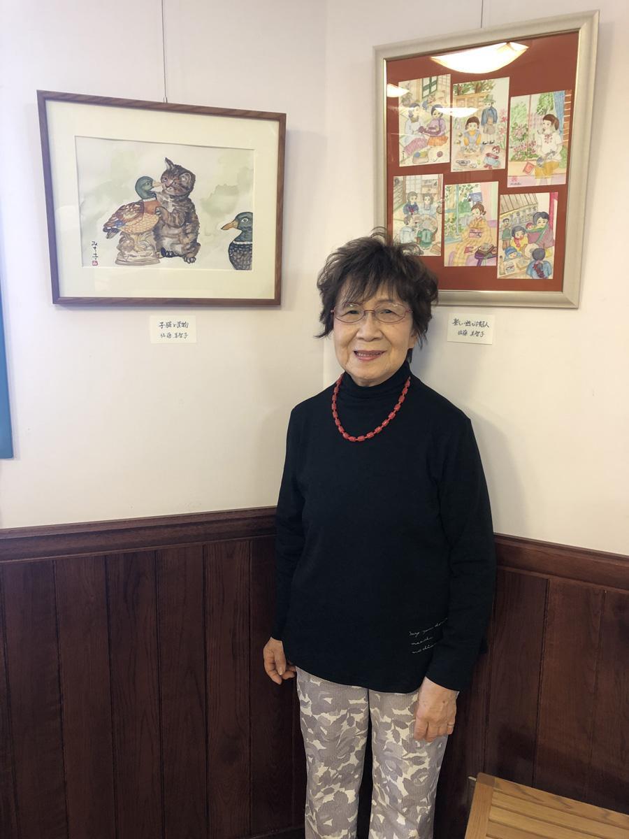 作品の前で笑顔の佐藤美智子さん