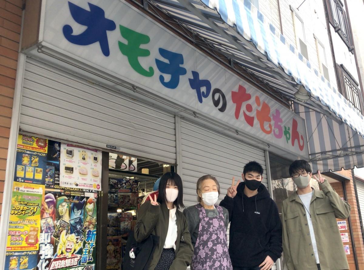 シャッターが下りた店の前で店主・金子影子さんと記念撮影する若者