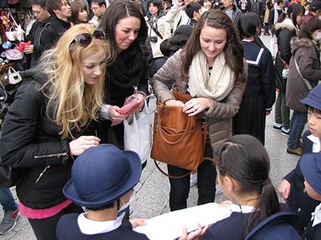 外国人観光客と交流する小学生たち