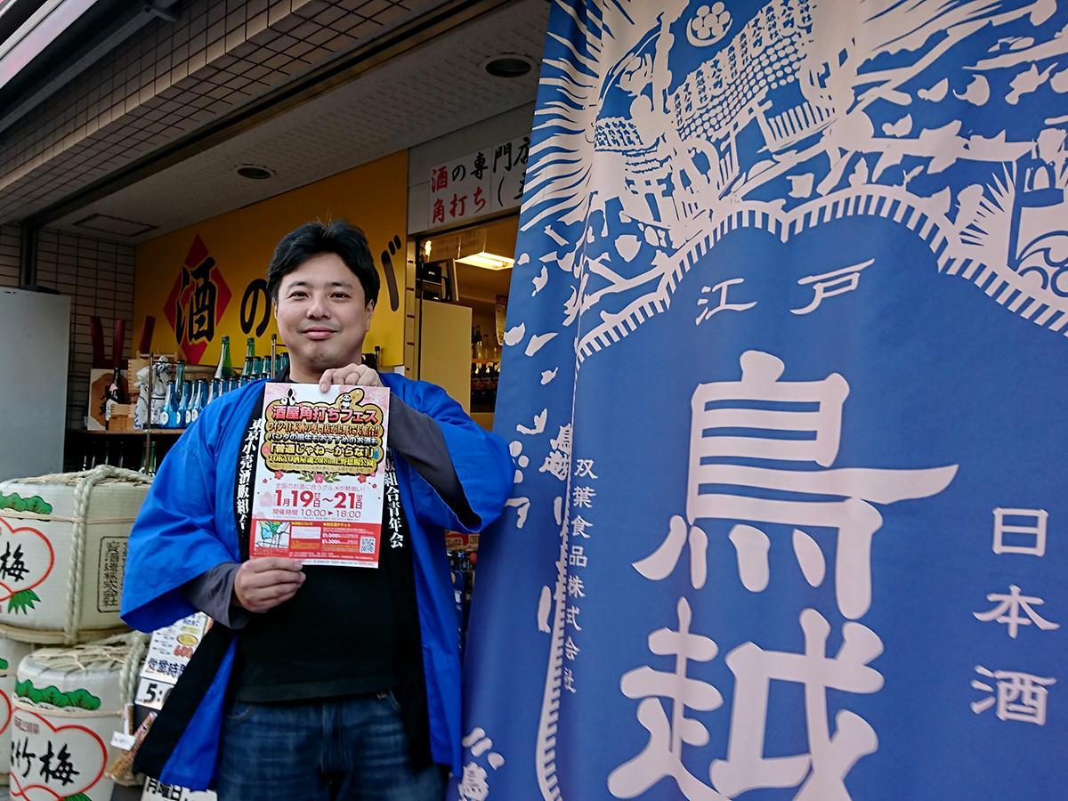 イベントチラシを掲げる実行委員長の関明泰さん
