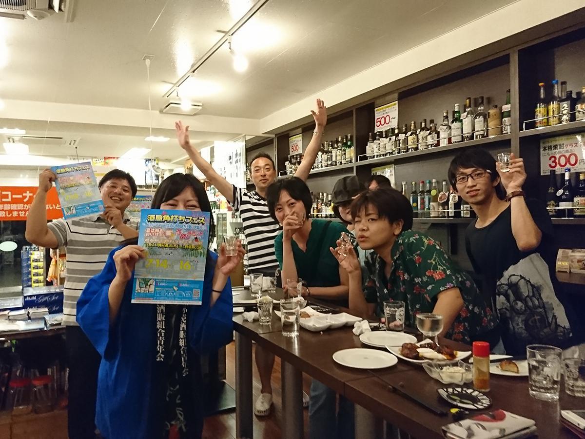 実行委員長の関明泰さん(左)の元に角打ちファンが集まる